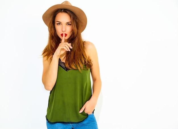 Jong modieus vrouwenmodel in toevallige de zomer groene kleren en bruine hoed met rode lippen die stiltegebaar met geïsoleerde vinger tonen ,.