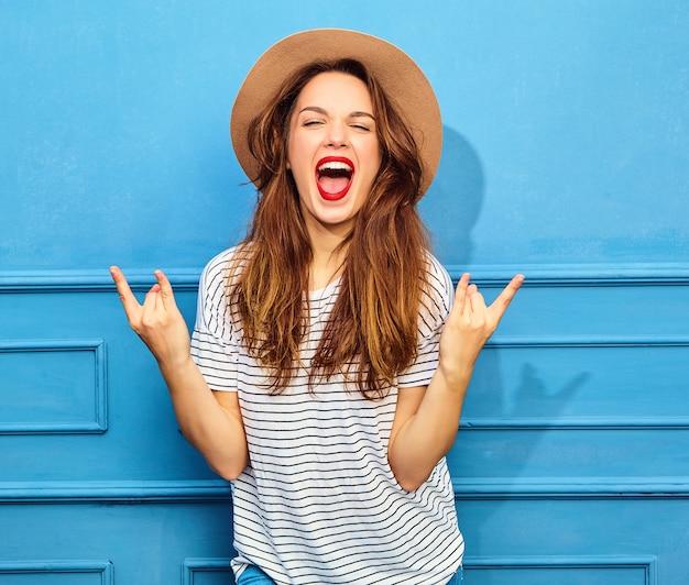 Jong modieus vrouwenmodel in toevallige de zomerkleren en bruine hoed met rode lippen, die dichtbij blauwe muur stellen. gillen en rock-'n-roll-teken tonen