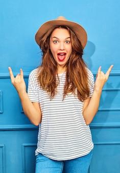 Jong modieus vrouwenmodel in toevallige de zomerkleren en bruine hoed met rode lippen, die dichtbij blauwe muur stellen. rock and roll-teken tonen