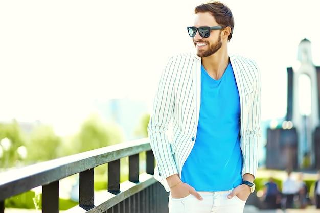Jong modieus zeker gelukkig knap zakenmanmodel die in kostuum hipster kleren in de straat in zonnebril lopen