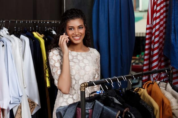 Jong mooi afrikaans meisje dat op telefoon in winkelcomplex spreekt.
