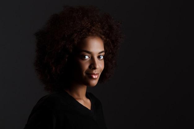 Jong mooi afrikaans meisje dat over donkere muur glimlacht