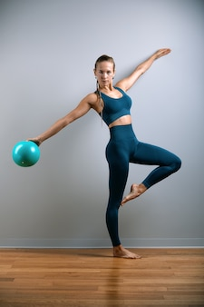 Jong, mooi, atletisch meisje doet oefeningen op fitball in de sportschool