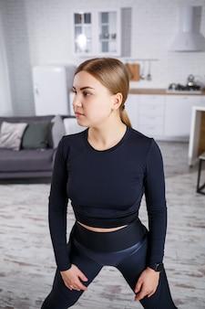 Jong mooi atletisch meisje in legging en een top doet rekoefeningen. gezonde levensstijl. de vrouw gaat thuis sporten.