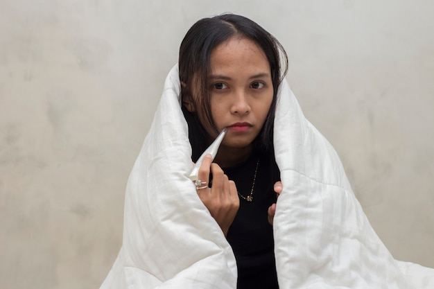 Jong mooi aziatisch meisje ziek en hoest in de gezondheidszorg van de slaapkamervrouwen