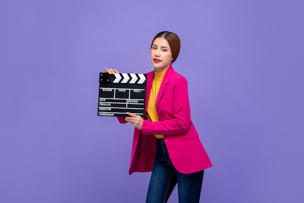 Jong mooi aziatisch vrouwenmodel die in kleurrijke kleren film clapperboard houden