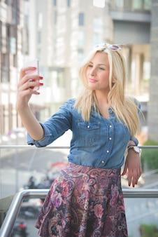 Jong mooi blonde kaukasisch meisje die een smartphone gebruiken die een selfie nemen