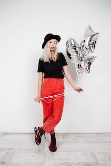 Jong mooi blondemeisje die zilveren baloons over witte muur houden.