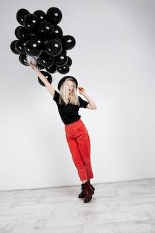 Jong mooi blondemeisje die zwarte baloons over witte muur houden.