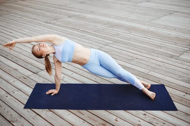 Jong mooi blondemeisje het beoefenen van yoga buiten.