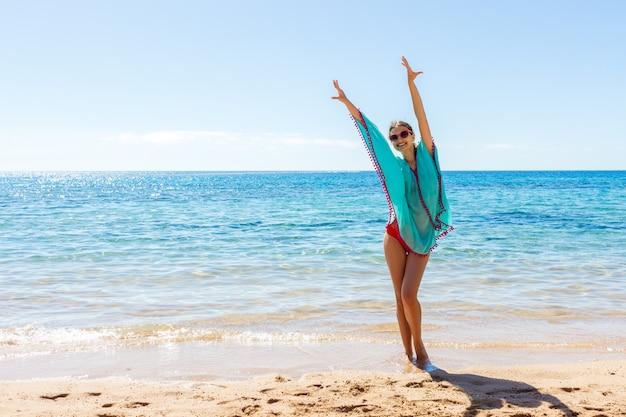 Jong mooi blondemeisje in glazen die pret op het strand hebben