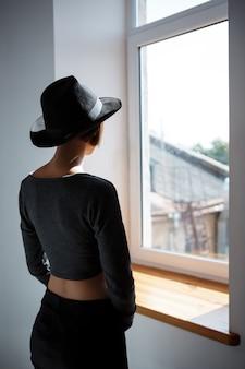Jong mooi donkerbruin meisje dat in hoed in venster kijkt.