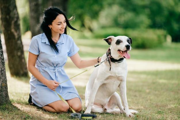 Jong mooi donkerbruin vrolijk meisje die in blauwe kleding haar aanbiddelijke hond in de zomerpark kussen