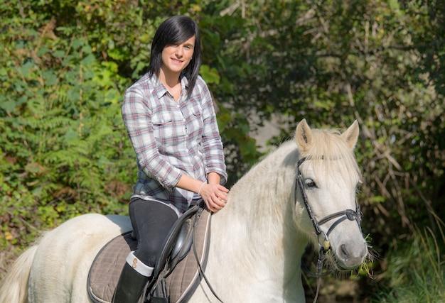 Jong mooi donkerbruin vrouw het berijden paard
