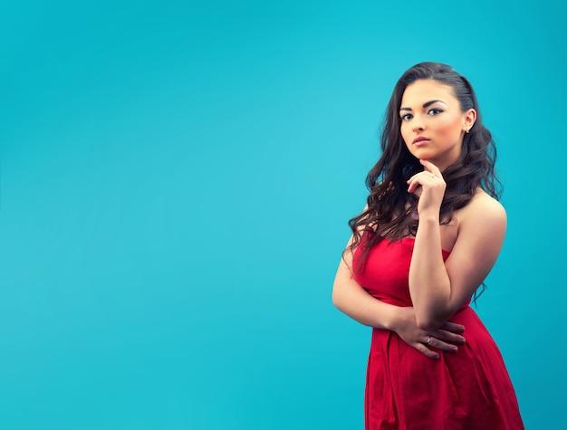 Jong mooi en ernstig meisje in een rode jurk, met make-up op een blauwe muur