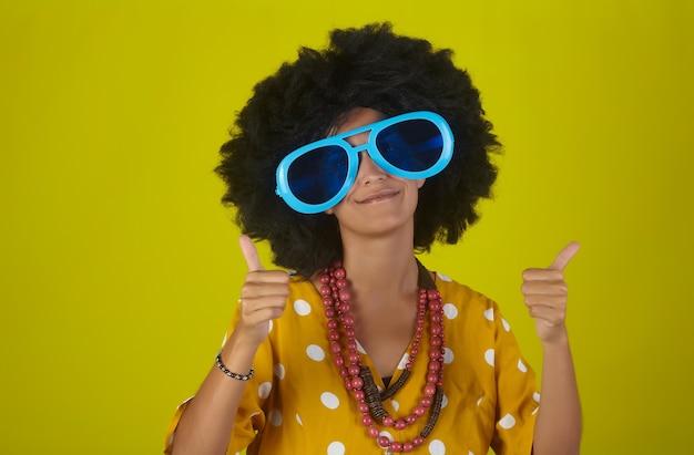 Jong mooi en glimlachend meisje met krullend afrokapsel en grappige glazen die duimen over gele achtergrond tonen