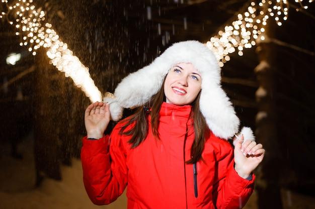 Jong mooi gelukkig glimlachend meisje dat witte gebreide bonthoed draagt