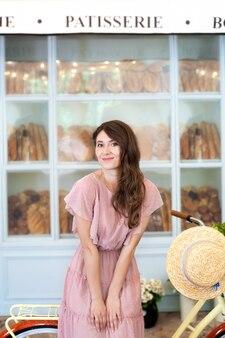 Jong mooi gelukkig meisje met lang krullend haar in een roze jurk in een straatkoffiehuis