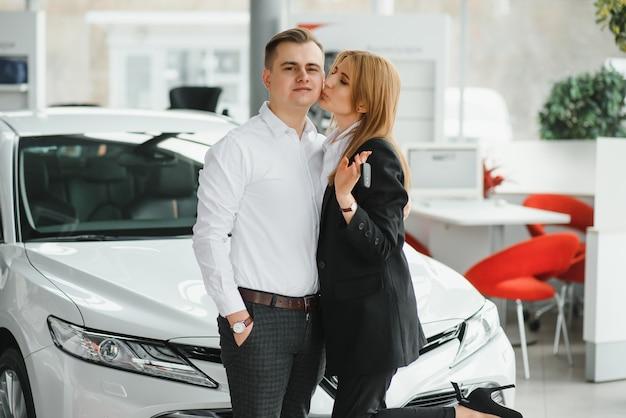 Jong mooi gelukkig paar dat een auto koopt. echtgenoot die auto voor zijn vrouw in een salon koopt. auto winkelen concept.