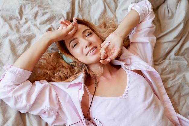 Jong mooi gembermeisje in oortelefoons die zich in bed na volledig geruste kielzog uitrekken.