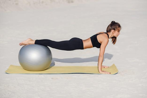 Jong mooi geschiktheidsmeisje die opdrukoefeningenoefeningen met geschikte bal op het strand doen. sport en een gezonde levensstijl concept.