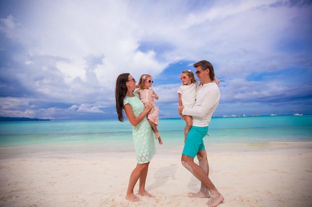 Jong mooi gezin met twee kinderen kijken elkaar op tropische vakantie