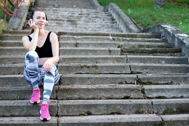 Jong mooi glimlachend slank sportief meisje dat op de treden situeert en naar muziek luistert.