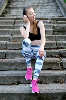 Jong mooi glimlachend slank sportief meisje die op de treden situeren en naar muziek luisteren. gezonde sport levensstijl.