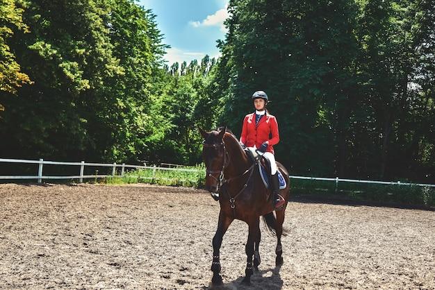Jong mooi jockeymeisje paard rit voorbereiden. hou van paarden. meisje berijden van een paard