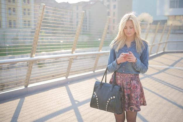Jong mooi kaukasisch blonde meisje in de stad