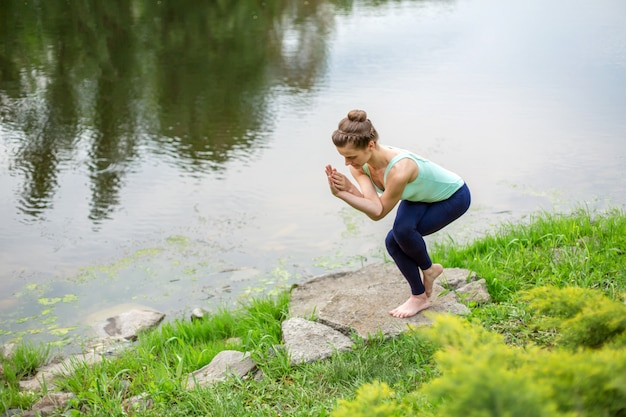 Jong mooi kaukasisch donkerbruin meisje dat yoga op een groen gazon doet tegen de achtergrond van de rivier