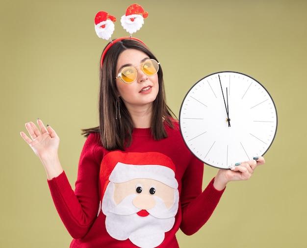 Jong mooi kaukasisch meisje die de trui van de kerstman en hoofdband met glazen dragen die klok houden opzoeken met lege hand geïsoleerd op olijfgroene achtergrond