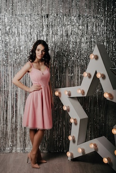 Jong mooi kaukasisch meisje in een roze kleding op een achtergrond van kerstmisdecor