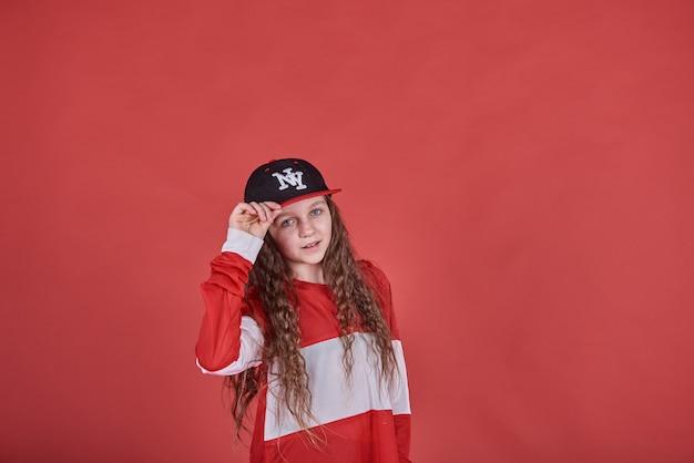 Jong mooi leuk meisje die op rode muur dansen, het moderne slanke de tiener van de hiphopstijl springen