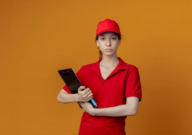 Jong mooi leveringsmeisje die in rood uniform en glb het klembord en de pen van de cameraholding bekijken die op oranje achtergrond met exemplaarruimte wordt geïsoleerd