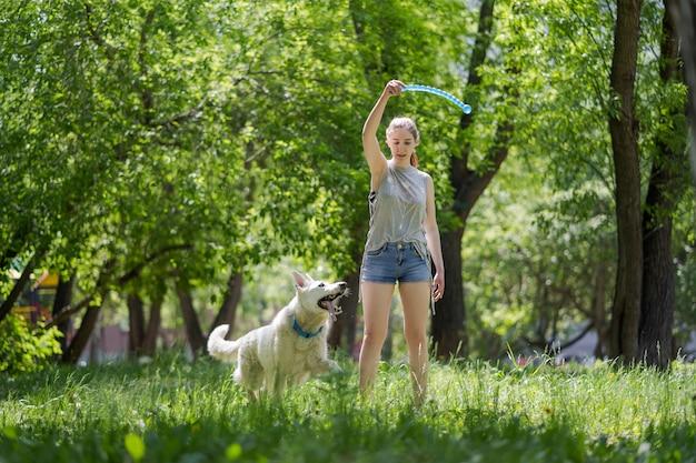 Jong mooi meisje dat aan haar hond in een park bij zonsondergang werpt