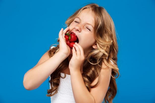 Jong mooi meisje dat aardbei over blauwe muur eet