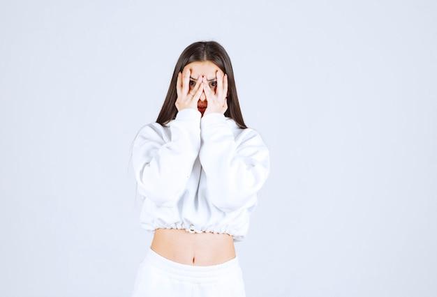 Jong mooi meisje dat door vingers op wit-grijs kijkt.