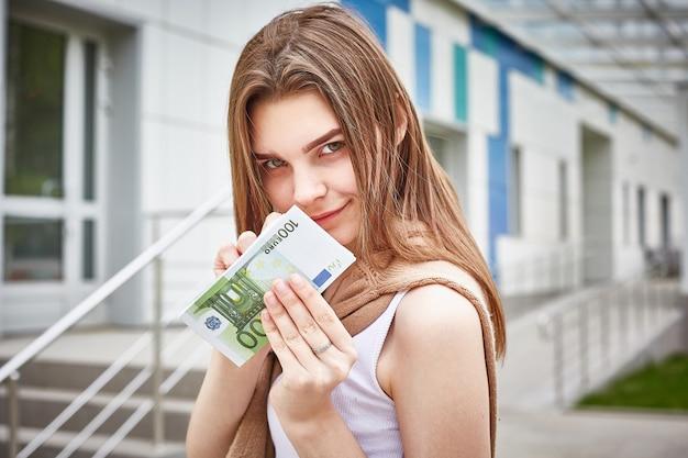 Jong mooi meisje dat een bundel van euro bankbiljetten in haar handen houdt