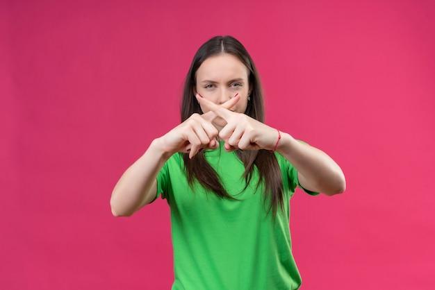 Jong mooi meisje dat een groen t-shirt draagt dat defensiegebaar maakt die wijsvingers kruist die met fronsend gezicht kijkt dat zich over geïsoleerde roze achtergrond bevindt