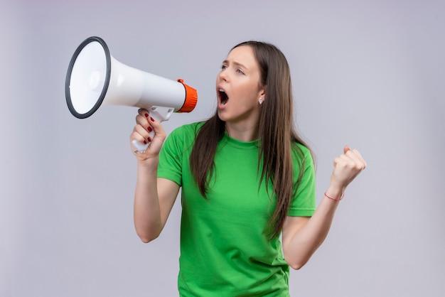 Jong mooi meisje dat een groene t-shirt draagt die aan emotionele en ongeruste megafoon schreeuwt die zich over geïsoleerde witte achtergrond bevindt