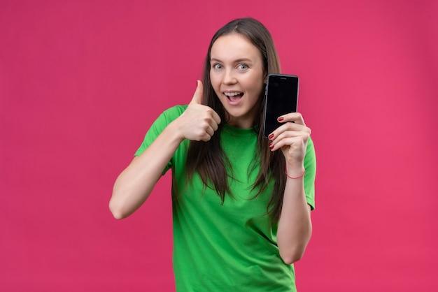 Jong mooi meisje dat een groene t-shirt draagt die de smartphone houdt die vrolijk glimlacht toont duimen omhoog die zich over geïsoleerde roze achtergrond bevinden