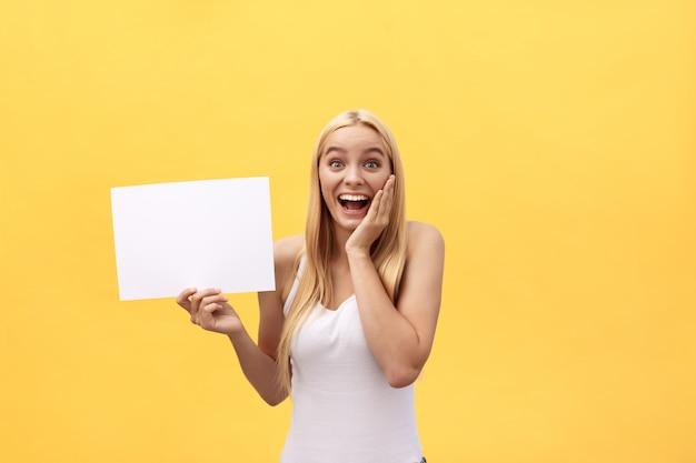 Jong mooi meisje dat en een leeg blad van document glimlacht houdt, dat op pastelkleur gele achtergrond wordt geïsoleerd.