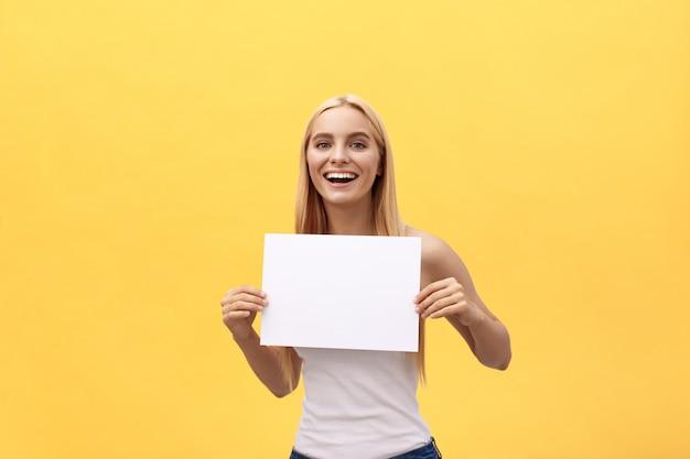 Jong mooi meisje dat en een leeg blad van document glimlacht houdt