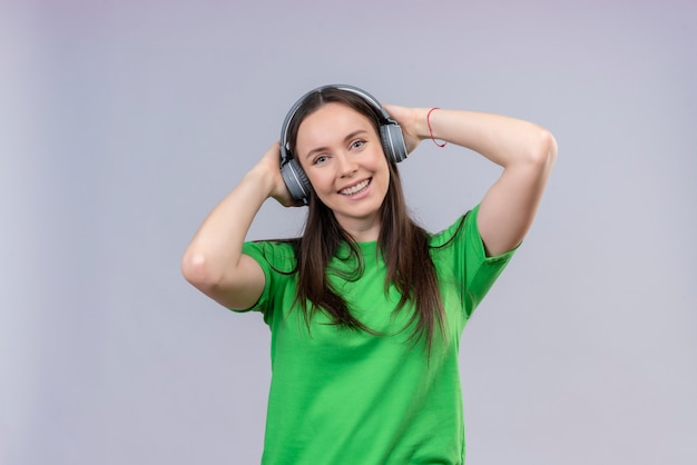 Jong mooi meisje dat groen t-shirt met hoofdtelefoons draagt die positief en gelukkig glimlachen genietend van favoriete muziek die zich over geïsoleerde witte achtergrond bevindt