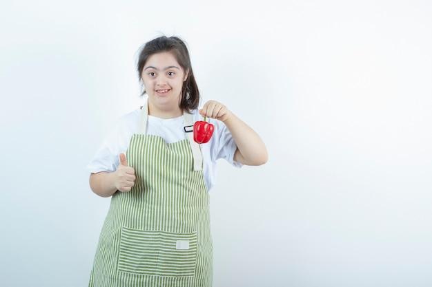 Jong mooi meisje dat in geruite schort rode paprika houdt en duim toont.