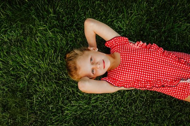 Jong mooi meisje dat in rood geregeld zwempak op groene open plek legt