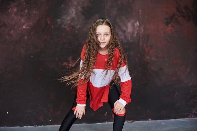 Jong mooi meisje dat in trendy kleren danst