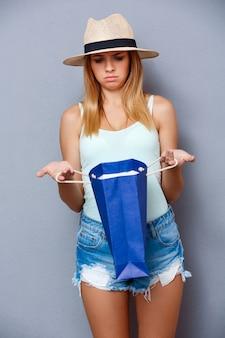 Jong mooi meisje dat kleurrijke zakken over grijze achtergrond houdt.
