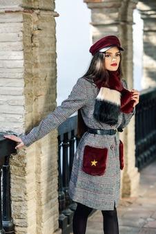 Jong mooi meisje dat met zeer lang haar weg in openlucht het dragen van de winterjas en glb kijkt